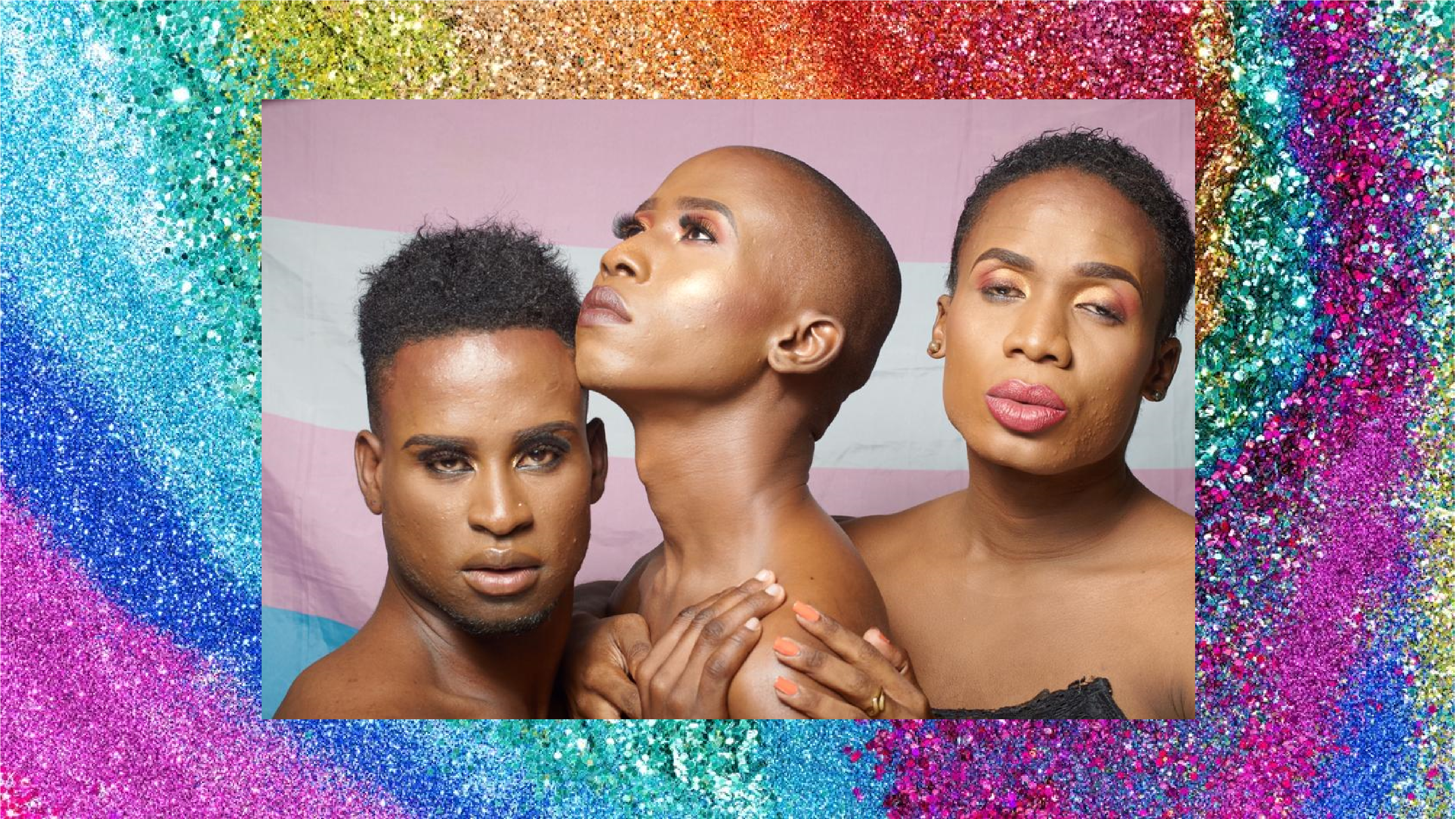 A large image takes up the upper part of the page, featuring three glamorously dressed and made up people embracing in front of a trans pride flag. Behind this image is another image, which creates a glittery rainbow border.